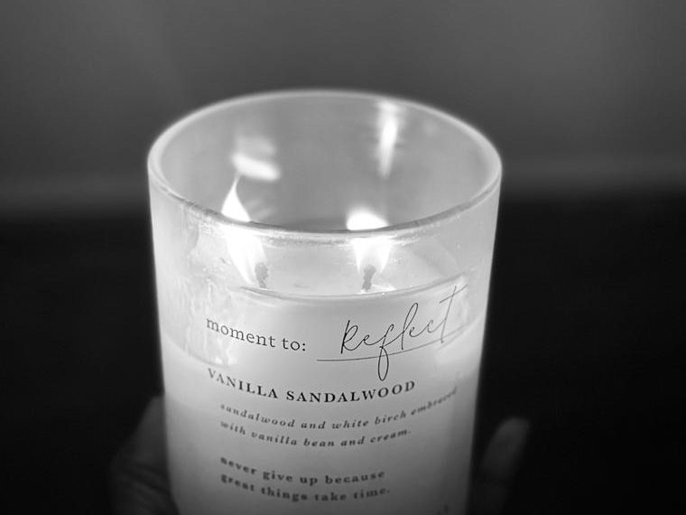 """A lit Candle with the words """"moment to reflect"""" written on it"""
